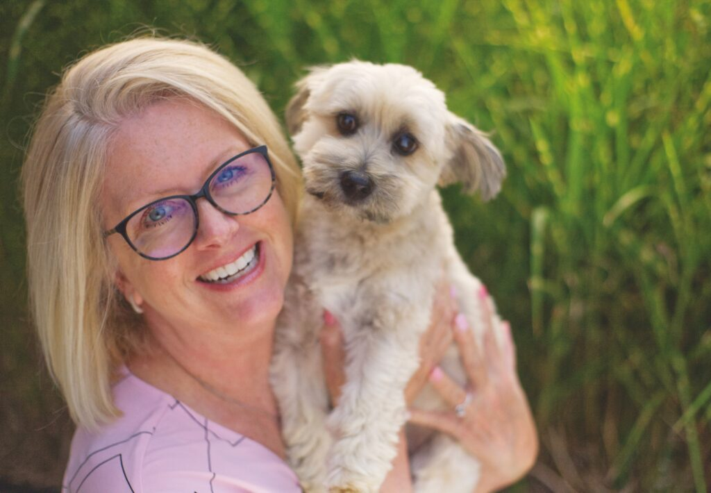 Kris Henderson and her dog Dezzy posing together.