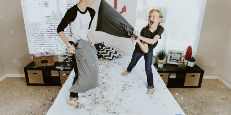 Two young boys having a pillow fight leading their parents to wonder how to stop feeling overwhelmed.