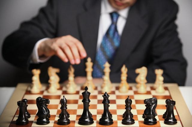 Man making a move on a chess set.
