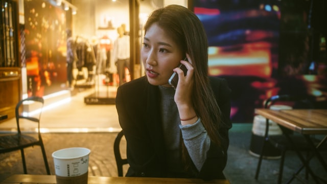 Woman making a phone call to schedule coaching about parenting stress.