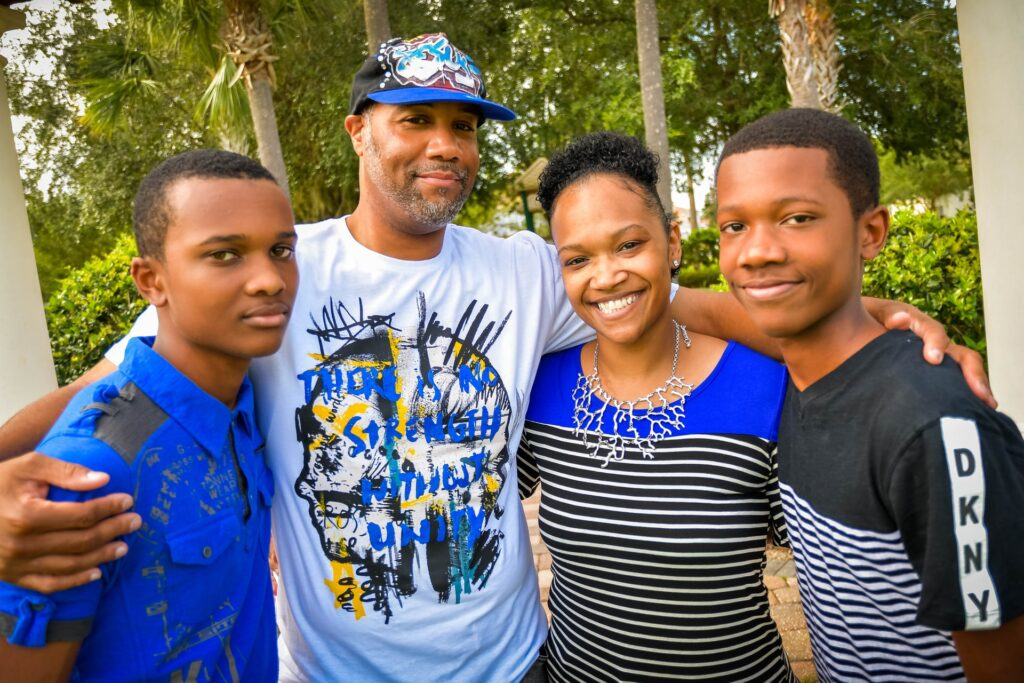 Black family of mom, dad and two teenagers enjoying being outside.