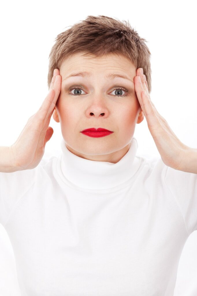 Woman with hand on each side of face stressing out.