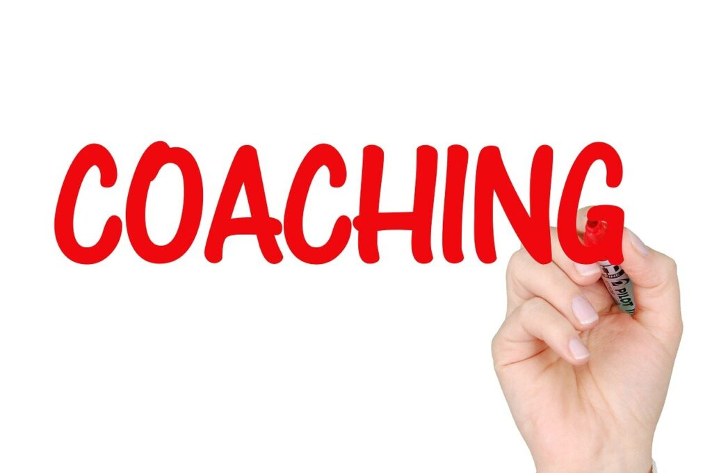 A hand holding a pen with the word COACHING