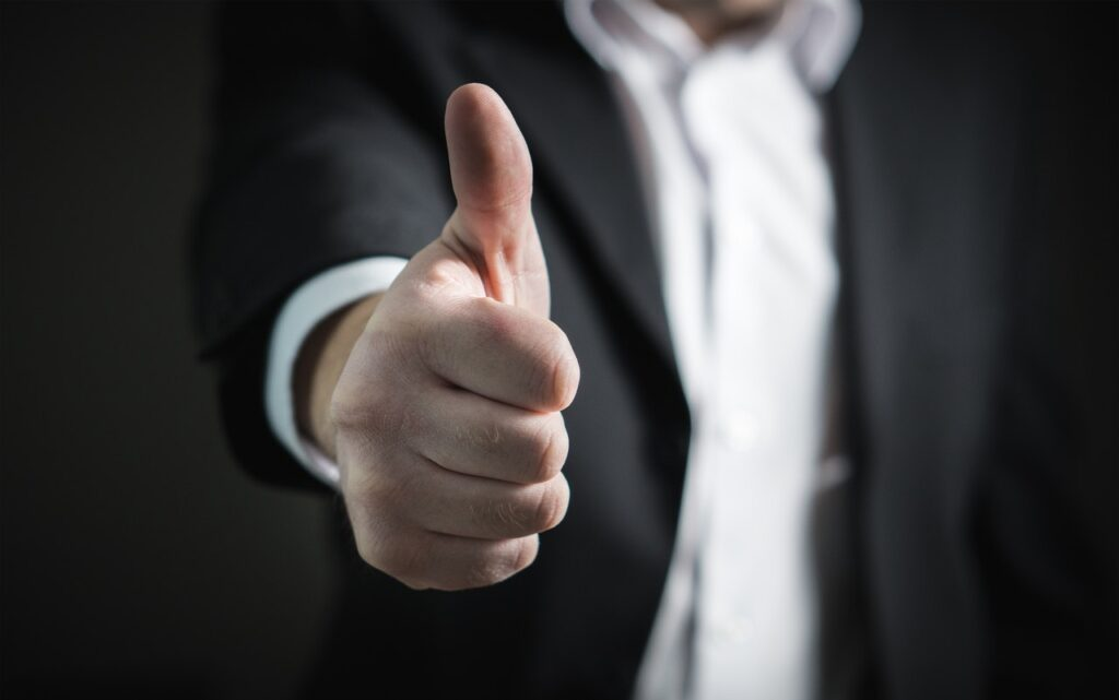 Man in suit showing a thumbs up