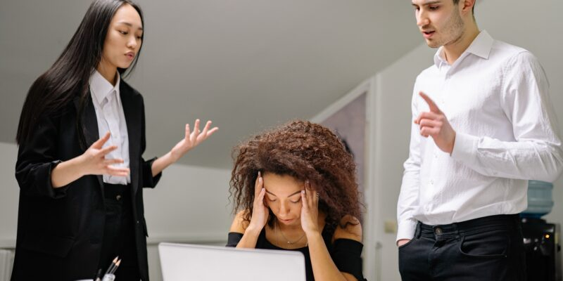 Young woman holding her head in her hands clearly overwhelmed at work.