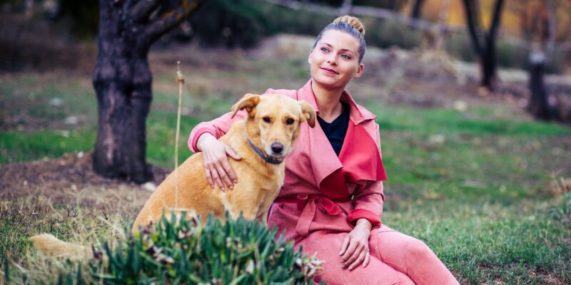 Smiling woman outside playing with her dog which is one of the stress and anxiety relief tips