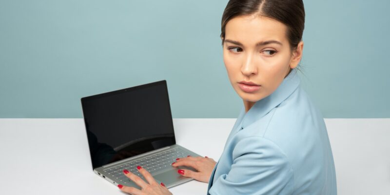 Women in in front of computer looking over her shoulder dealing with return to work anxiety after Covid-19