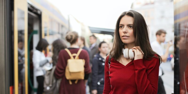 Anxious looking woman wearing a red shirt in a crowd wanting the best way to calm her anxiety.