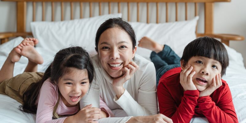 Smiling mom, son and daughter laying together on bed.