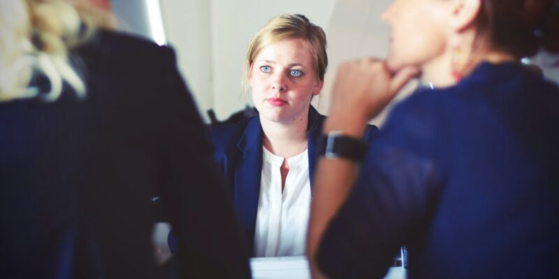 Woman with poor coping skills looking at anxious sitting with two co-worker.