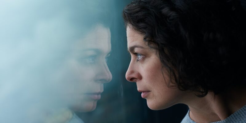 Woman looking at her reflection in window wondering how to find her best rememdy for anxiety.