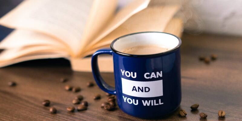 Blue coffee mug with an inspirational anxiety relief quote written on it sitting on a table.